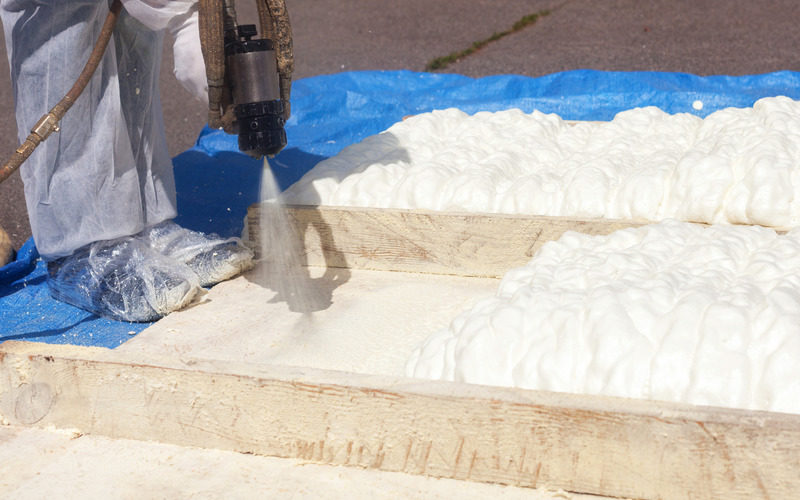 Technician spraying foam insulation using Plural Component Spray Gun. Spraying polyurethane foam for roof
